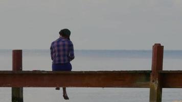 mulher sentada e escrevendo à beira-mar | filme de arquivo grátis video