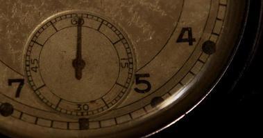 Escena oscura de primer plano de la manecilla del reloj de segundos que se mueve sesenta segundos en un lapso de tiempo de 4k video