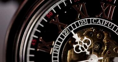 Extreme close up of pocket watch with white hands and exposed machinery working twenty seven seconds in 4K time lapse video