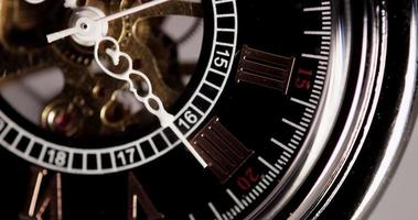 Cierre extremo del reloj de bolsillo con manecillas blancas y maquinaria expuesta trabajando cuarenta segundos en un lapso de tiempo de 4k video