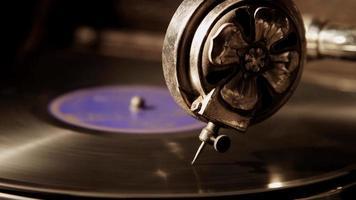 close-up extremo filmado com luz do lado esquerdo da vitrola, focando em uma agulha de reprodutor decorada tocando um disco de vinil em 4k
