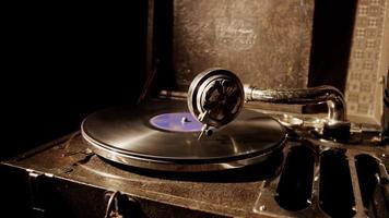 Mittlere statische Aufnahme eines klassischen Plattenspielers und einer alten Vinylscheibe, die sich mit Deckenbeleuchtung in 4k dreht
