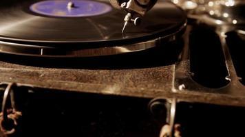 vertikale Schwenkaufnahme eines antiken Plattenspielers mit einer alten Vinylscheibe, die sich in 4k dreht