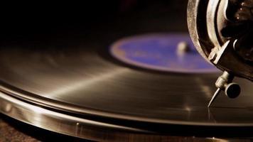 close-up extremo da agulha reprodutora tocando um disco de vinil com pequenos reflexos leves em 4k