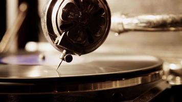 close-up extremo da agulha do reprodutor tocando um disco de vinil com pouco brilho do lado esquerdo em 4k
