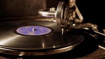 dunkle mittlere Aufnahme eines Plattenspielers mit Vinylscheibe, die in 4k von der linken Seite der Szene beleuchtet wird