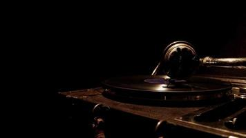 Dark traveling shot from left to right of classic record player working with soft overhead lighting in 4K