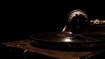 Slow traveling shot from left to right of vintage nusic device playing a disc with soft overhead lighting in 4K
