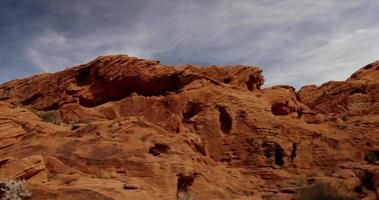 Traveling shot of red rock hill in desert landscape with cirrus clouds in blue sky in 4K