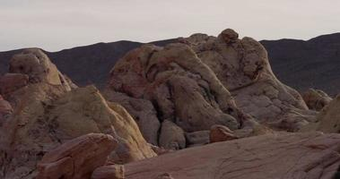 Panning shot going to the left of ligtht red rocks in desertic landscape with mountains  in background in 4K