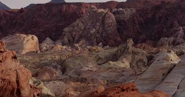 Toma panorámica vertical bajando mostrando hermosas rocas rojas con diferente saturación en el paisaje desértico en 4k video