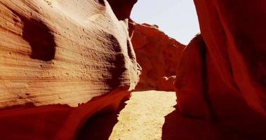 bela foto de viagem dentro de uma formação geológica mostrando paredes laranja e reflexo do sol em 4k