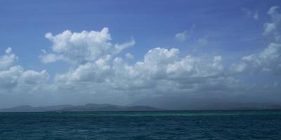 timelapse do mar com bela nuvem movendo-se sobre as ondas com montanhas ao fundo em 4k video