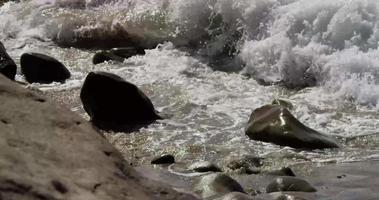 rompiendo olas en una playa rocosa