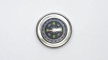 compass on white surface top view