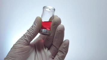 Hombre preparando un líquido morado en un frasco pequeño video