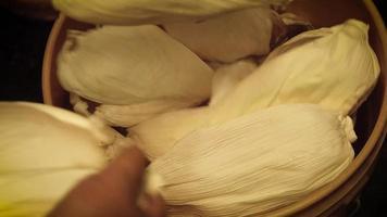 mujeres preparando hojas de maíz para tamales video