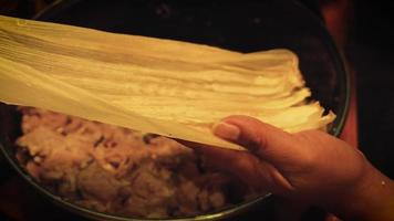 Woman Preparing A Green Sauce Tamale With Pork Meat And Beans