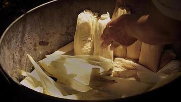 mujer colocando tamales en la olla
