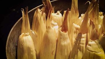 Detalle de mujer colocando tamales en la olla