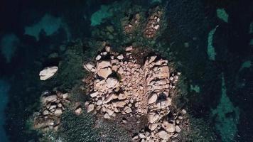 volando indietro sopra le rocce nel mare in 4K