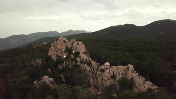 volando hacia una roca con cabañas en 4k video
