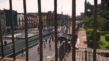 People And Old Buildings Near The Main Square Of Mexico City Through Railing