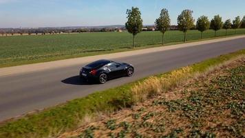 Drone follows a sports car from right - close shot in 4K