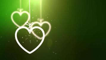 Corazones de San Valentín de papel cayendo colgando sobre una cuerda fondo verde