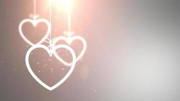 Corazones de San Valentín de papel cayendo colgando de una cadena de fondo blanco. video