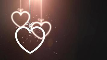 Corazones de San Valentín de papel cayendo colgando sobre una cuerda fondo negro video