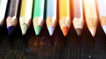 sobre un fondo de madera lápices multicolores. lápices de colores brillantes de cerca. macro. disparo macro video