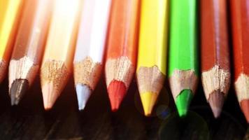 sur un fond en bois crayons multicolores. crayons de couleur vive se bouchent. macro. prise de vue macro