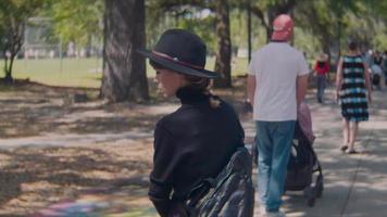 Vista trasera de una mujer caminando por el parque con mucha gente video