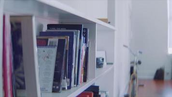 mujer yong selecciona un libro de una estantería