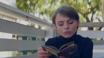 Cerca de joven leyendo un librito en una terraza