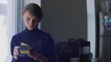 Mujer joven leyendo un pequeño libro en la cocina