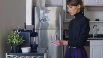Young woman makes herself an espresso in her kitchen video