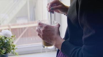 gros plan d'une jeune femme en remuant son café du matin video