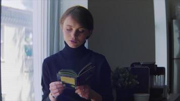jovem pesquisando informações em um livro perto de uma grande janela video