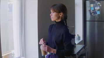 mujer mirando por la ventana de la cocina