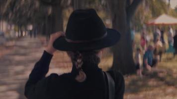 Vista trasera de una mujer caminando en el parque peinándose