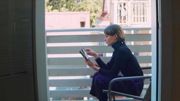 jovem lendo e tomando café em um terraço video