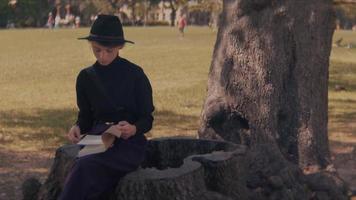 mulher em um parque escrevendo em seu caderno video