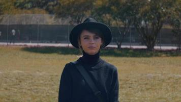 vista frontal de uma jovem com um chapéu caminhando em um parque video