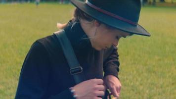 Mujer buscando un libro en su bolso y relajándose en el césped