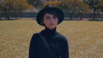 vista frontal de uma jovem com um chapéu, caminhando na grama video