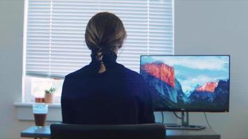 vista trasera, de, un, mujer joven, trabajando, en, ella, computadora