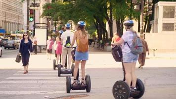 Menschen auf Segways überqueren die Straße in Chicago video