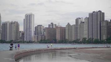 Skyline Of Chicago City With People Walking On A Dock